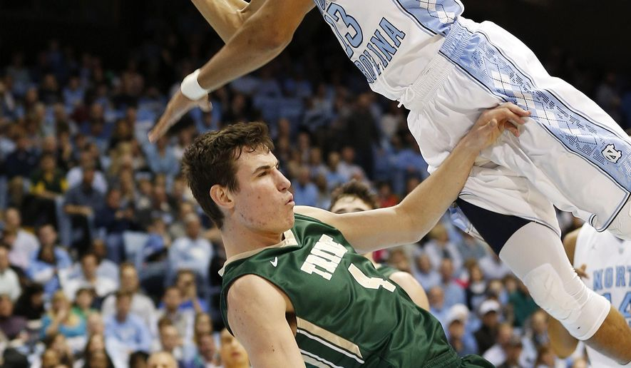 North Carolina's J.P. Tokoto, top, goes to the basket against William & Mary's Omar Prewitt during the first half of an NCAA college basketball game Tuesday, Dec. 30, 2014, in Chapel Hill, N.C. (AP Photo/Ellen Ozier)