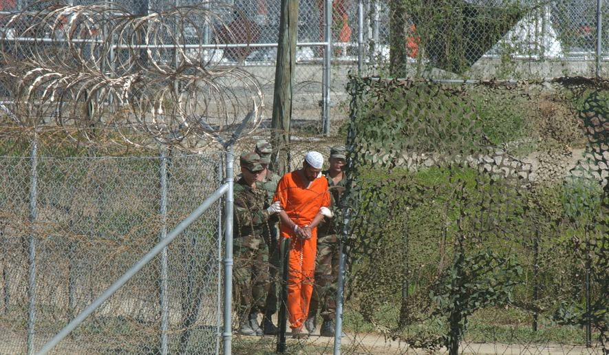 In this March 1, 2002, file photo, a detainee is escorted to interrogation by U.S. military guards at Camp X-Ray at Guantanamo Bay U.S. Naval Base, Cuba. (AP Photo/Andres Leighton, File)