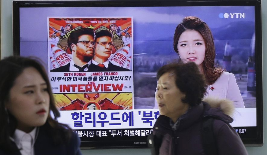 """FILE- In this Monday, Dec. 22, 2014, file photo, people walk past a TV screen showing a poster of Sony Picture's """"The Interview"""" in a news report,  at the Seoul Railway Station in Seoul, South Korea. A South Korean activist said Wednesday, Dec. 31, 2014, that he will launch balloons carrying DVDs of Sony's """"The Interview"""" toward North Korea to try to break down a personality cult built around the country's leader Kim Jong Un. (AP Photo/Ahn Young-joon, File)"""