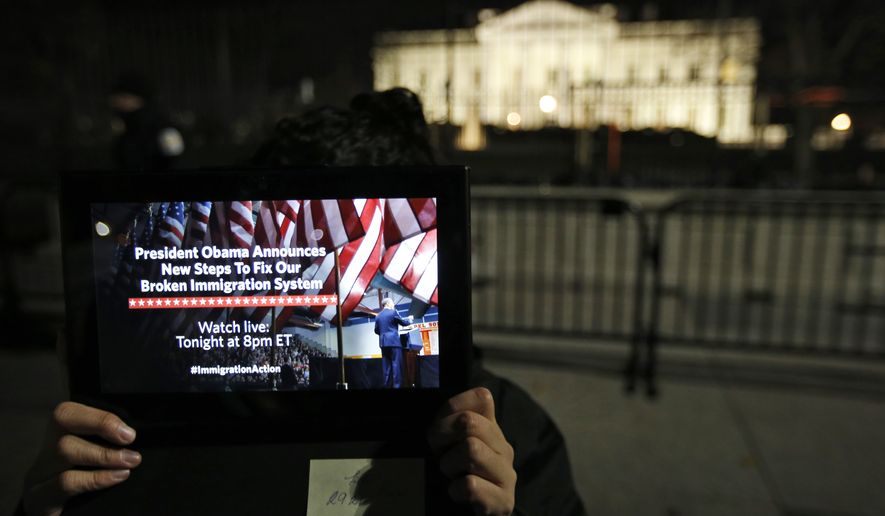 A supporter holds a tablet in front of the White House in Washington during a demonstration before President Obama's immigration address on Nov. 20, 2014 . President Barack Obama announced executive actions on immigration during a nationally televised address. (Associated Press) **FILE**