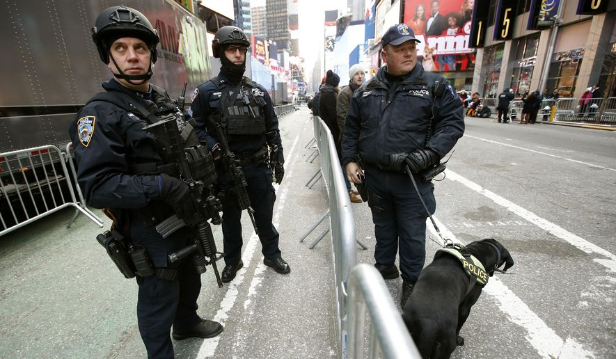 New York city police officers armed with heavy weapons pause for a break in between patrolling Times Square on New Year's Eve in New York, Wednesday, Dec. 31, 2014.  (Associated Press) ** FILE **