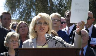 FILE - In a March 12, 2014 file photo, Arizona Gov. Jan Brewer holds a copy of the Medicaid Restoration Plan draft bill at the Capitol in Phoenix. The Arizona Supreme Court on Wednesday, Dec. 31, 2014, allowed a lawsuit challenging Brewer's Medicaid expansion plan to move forward, a decision that deals a major blow to the outgoing governor's signature achievement. The high court agreed that 36 Republican lawmakers can sue Brewer over the legality of a hospital assessment that funds the expansion plan. (AP Photo/Matt York, File)