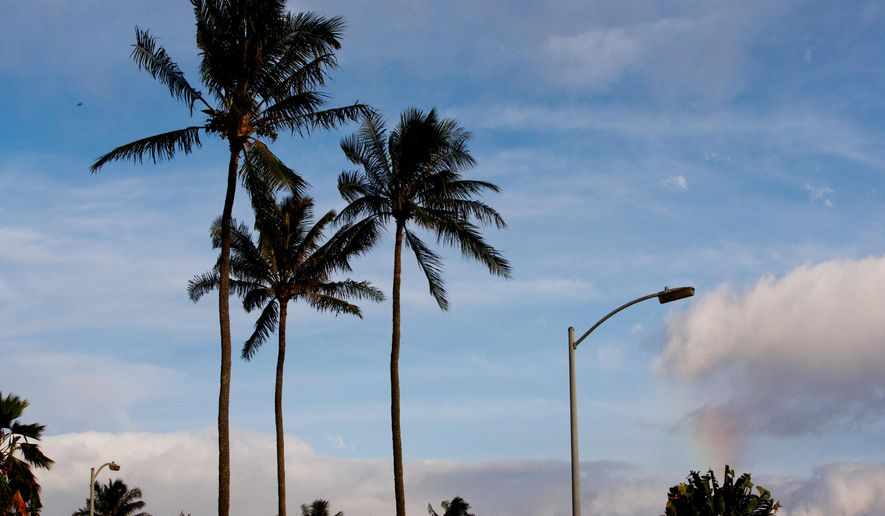 A faint rainbow appears to emanate from a street light before the arrival of a motorcade carrying President Barack Obama to the gym, Wednesday, Dec. 31, 2014, from his rental home in Kailua, Hawaii during the Obama family vacation. (AP Photo/Jacquelyn Martin)