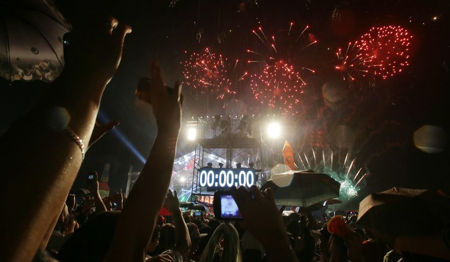 Crowds cheer as the countdown hits zero and fireworks begin during a New Year's Day celebration at the Quezon Memorial Circle in suburban Quezon city, north of Manila, Philippines on Thursday, Jan. 1, 2015. (AP Photo/Aaron Favila)