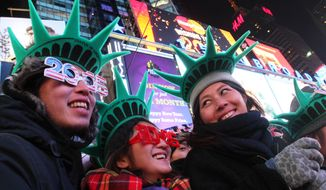 Yuko Yamagata, right, from Osaka, Japan, and other revelers take part in the New Year's Eve festivities Wednesday Dec. 31, 2014, in New York's Times Square. (AP Photo/Tina Fineberg)