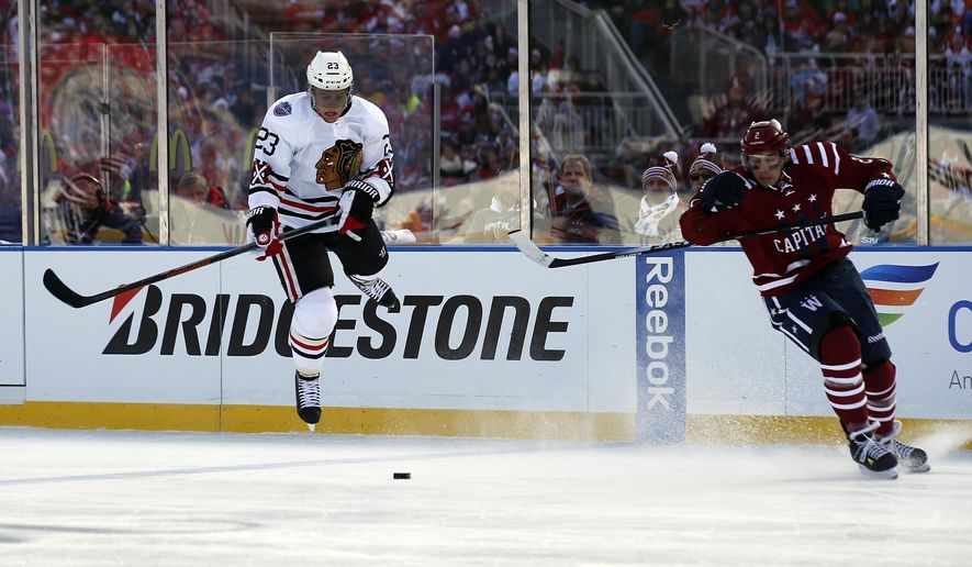 Chicago Blackhawks right wing Kris Versteeg (23) jumps to stay with the puck as Washington Capitals defenseman Matt Niskanen (2) defends, in the first period of the Winter Classic outdoor NHL hockey game at Nationals Park, Thursday, Jan. 1, 2015, in Washington. (AP Photo/Alex Brandon)