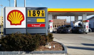 Cars fill up at the pumps at a Shell station near downtown Detroit, where the sign shows the price at $1.899 a gallon on Thursday, Jan. 1, 2015. AAA Michigan said that the average cost of self-serve unleaded gasoline in the state was $1.97 a gallon, the first time the price has fallen below $2 a gallon since March 2009 and down 9 cents since the beginning of the week. (AP Photo/David N. Goodman)