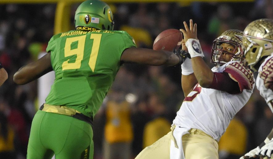 Oregon linebacker Tony Washington, left, knocks the ball away from Florida State quarterback Jameis Winston, right, before going on to score during the second half of the Rose Bowl NCAA college football playoff semifinal, Thursday, Jan. 1, 2015, in Pasadena, Calif. (AP Photo/Mark J. Terrill)