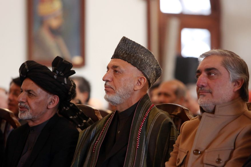 Afghan President Ashraf Ghani, left, former President Hamid Karzai,  center, and Chief Executive Abdullah Abdullah, right, attend a ceremony marking the completion of security transition to Afghan security forces in Kabul, Thursday, Jan. 1, 2015. Afghan police are investigating a rocket strike on a wedding party that killed at least 28 people, many of them women and children, an official said Thursday, as President Ashraf Ghani marked the country's transition to full sovereignty after the 13-year international military mission to rid Afghanistan of insurgents officially ended. (AP Photo/Rahmat Gul)