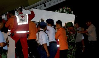 "Members of the National Search And Rescue Agency carry a coffin containing the body of one of the victims on board the ill-fated AirAsia Flight 8501 to transfer to Surabaya at the airport in Pangkalan Bun, Indonesia, Thursday, Jan. 1, 2015. Searchers were racing ""against time and weather"" Thursday to recover the dead from the crash, with a window of good conditions slammed shut by another onslaught of wind and heavy rain. (AP Photo/Tatan Syuflana)"