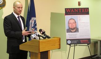 """Nathan Emery, Homeland Security Investigations agent in charge, stands next to a poster of Jeremiah Malfroid, a 33-year-old California man whose name and image were transmitted by the """"Operation Predator"""" app in connection with a child pornography sting.  (AP Photo/Andrew Welsh-Huggins)"""