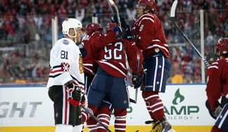 Washington Capitals center Nicklas Backstrom (19), from Sweden, defenseman Mike Green (52) and left wing Alex Ovechkin (8), from Russia, surround right wing Troy Brouwer (20) after Brouwer scored the winning goal as Chicago Blackhawks right wing Marian Hossa (81), from Slovakia, looks on in the third period of the Winter Classic outdoor NHL hockey game at Nationals Park, Thursday, Jan. 1, 2015, in Washington. The Capitals won 3-2. (AP Photo/Alex Brandon)