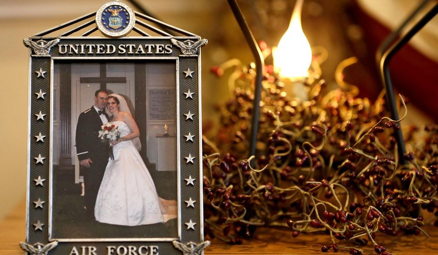 ADVANCE FOR USE MONDAY, JAN. 5, 2015, AND THEREAFTER- This Dec. 16, 2014 photo shows the wedding photo of Army widow, Aimee Wriglesworth, and her late husband, Chad, on display in her home in Bristow, Va.  Wriglesworth lost her husband, an Army Major to cancer in 2013. By the hundreds, other widows, widowers, parents, siblings and children are sharing accounts of their grief as part of the largest study ever of America's military families as they go through bereavement. (AP Photo/Steve Helber)