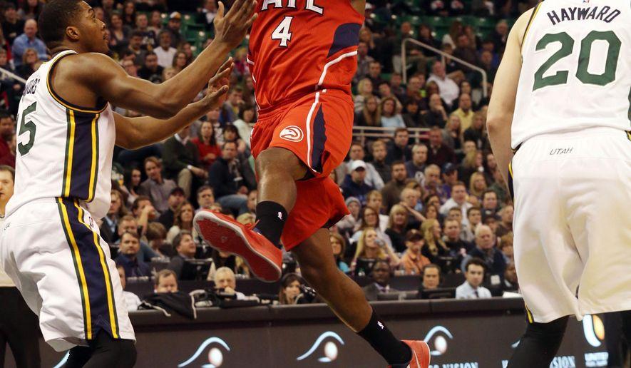 Atlanta Hawks' Paul Millsap (4) passes the ball as Utah Jazz's Derrick Favors (15) and Gordon Hayward (20) defend in the first half of an NBA basketball game on Friday, Jan. 2, 2015, in Salt Lake City. (AP Photo/Kim Raff)