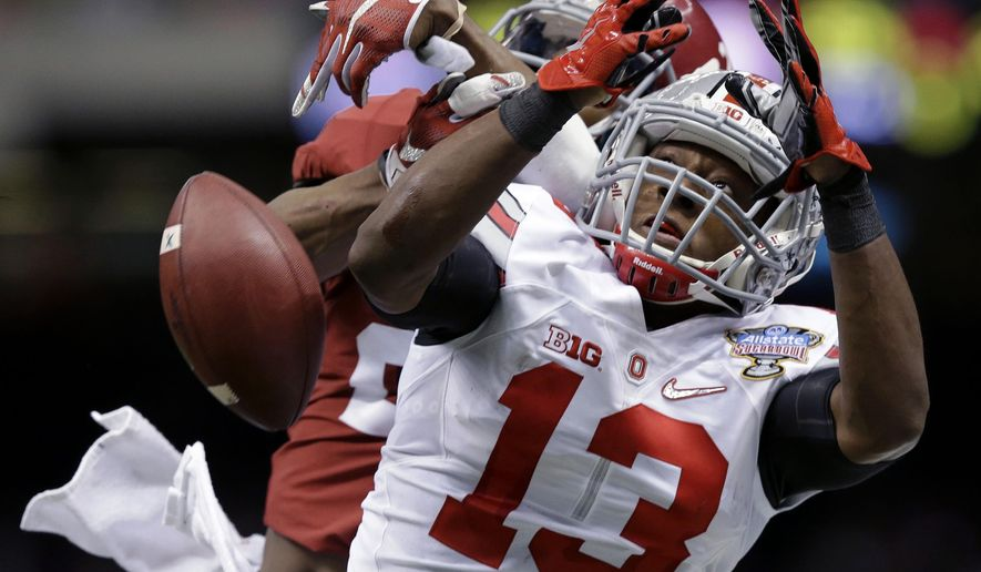 Ohio State cornerback Eli Apple (13) breaks up a desperation pass intended for Alabama wide receiver DeAndrew White (2) in the final minute of the second half of the Sugar Bowl NCAA college football playoff semifinal game, Thursday, Jan. 1, 2015, in New Orleans. (AP Photo/Brynn Anderson)