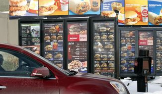 In this Jan. 26, 2009, file photo, a customer looks at the menu at a McDonald's drive-thru in Williamsville, N.Y. (AP Photo/David Duprey, File)