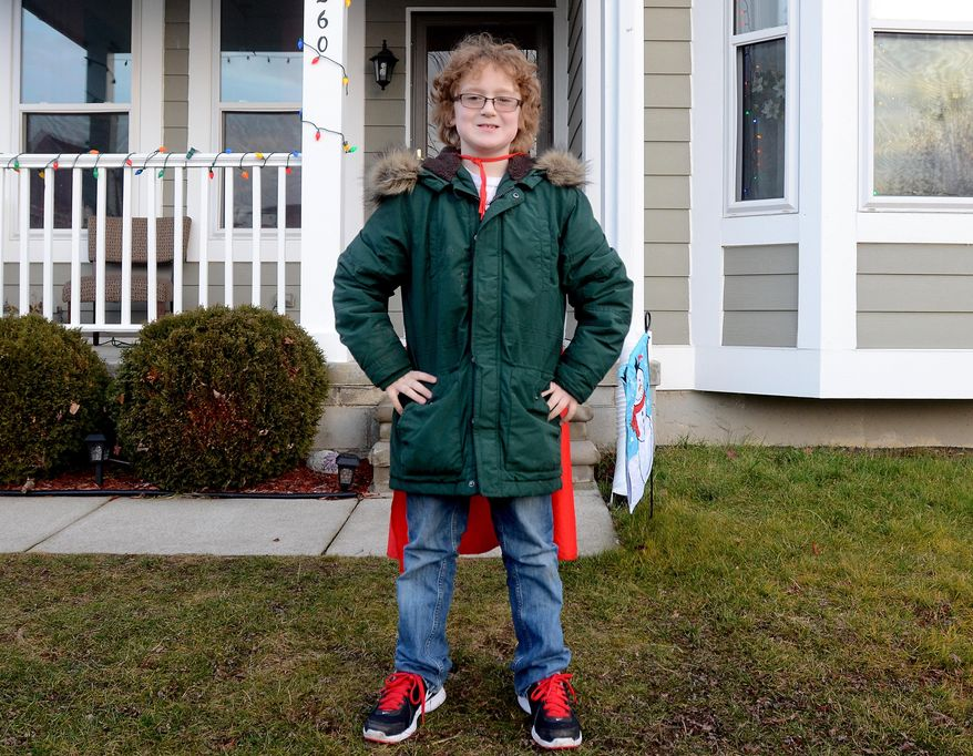 In this Monday, Dec. 15, 2014 photo, Ewan Drum poses with his cape at his home in New Haven, Mich. Drum is the founder of Super Ewan, a nonprofit to help the homeless. (AP Photo/The Port Huron Times Herald, Andrew Jowett) NO SALES