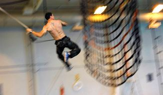 A Navy SEAL candidate traverses a Naval Special Warfare obstacle course at Little Creek, Va., on May 11, 2013. (U.S. Navy)