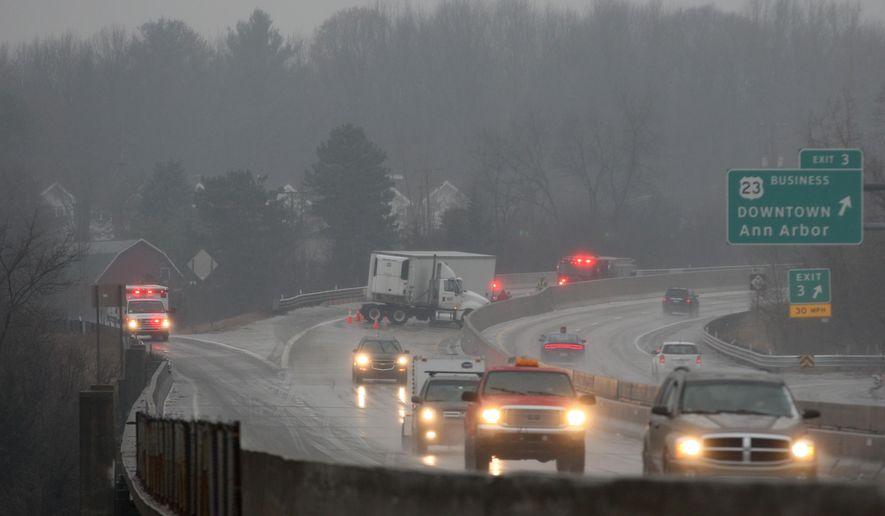 A truck is stalled on M14 in Ann Arbor, Mich., during a rainstorm that made for bad road conditions on Saturday, Jan. 3, 2014. (AP Photo/The Ann Arbor News, Patrick Record)