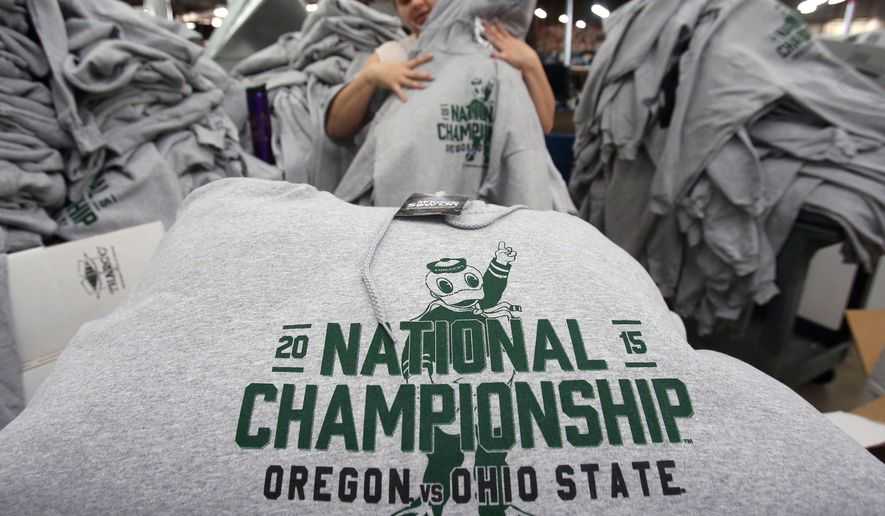 Katie Marie Snyder folds sweatshirts before packing them in boxes to be shipped from McKenzie Sew On in Springfield, Ore., on Friday, Jan.  2, 2015, to The Duck Store on the University of Oregon campus. Production was ramped up for the sweatshirts and other commemorative wear after Oregon's 59-20 Rose Bowl victory over Florida State. Oregon will face Ohio State in the first College Football Playoff championship game, on Jan. 12. (AP Photo/The Register-Guard, Andy Nelson)