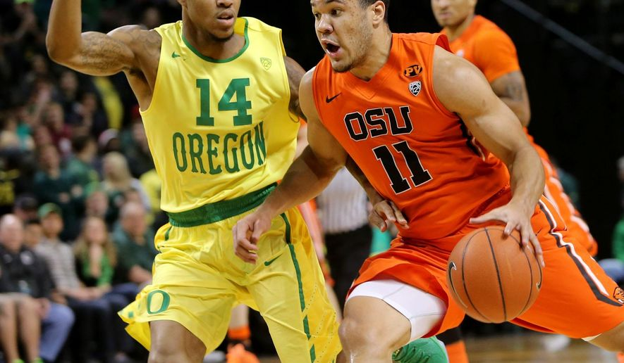Oregon's Ahmaad Rorie, left, pressures Oregon State's Malcolm Duvivier as he brings the ball up during the first half of an NCAA college basketball game in Eugene, Ore., Saturday, Jan. 3, 2015. (AP Photo/Chris Pietsch)