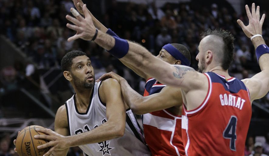 San Antonio Spurs' Tim Duncan, left, is pressured by Washington Wizards' Paul Pierce, center, and Marcin Gortat (4) during the second half of an NBA basketball game, Saturday, Jan. 3, 2015, in San Antonio. (AP Photo/Eric Gay)