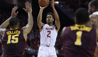 Maryland guard Melo Trimble, shoots as Minnesota forward Maurice Walker defends during the second half of  an NCAA college basketball game Saturday, Jan. 3, 2015, in College Park, Md. Maryland won 70-58. (AP Photo/Gail Burton)