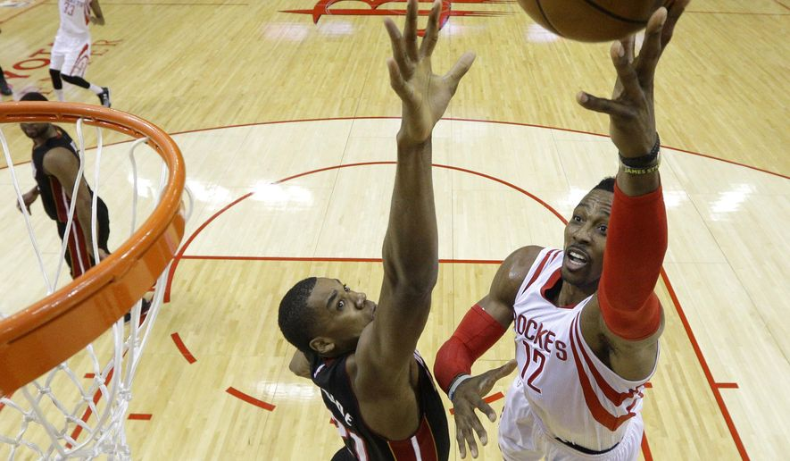 Houston Rockets' Dwight Howard (12) goes up for a shot as Miami Heat's Hassan Whiteside (21) defends during the first half of an NBA basketball game Saturday, Jan. 3, 2015, in Houston. (AP Photo/David J. Phillip)