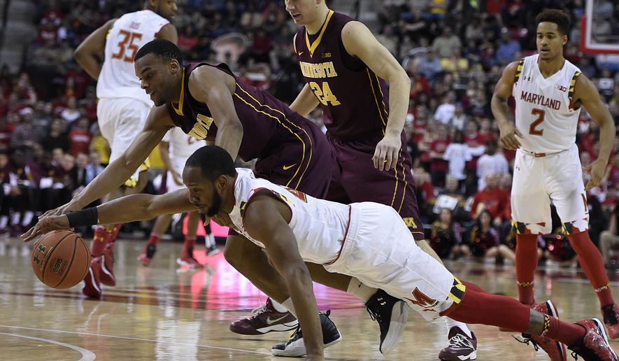 Maryland guard Dez Wells, bottom, and Minnesota guard Andre Hollins reach for a loose ball during the second half of  an NCAA college basketball game Saturday, Jan. 3, 2015 in College Park, Md. Maryland won 70-58.(AP Photo/Gail Burton)