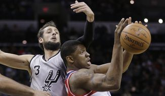 San Antonio Spurs' Marco Belinelli, left, and Washington Wizards' Bradley Beal, right, battle for a rebound during the first half of an NBA basketball game, Saturday, Jan. 3, 2015, in San Antonio. (AP Photo/Eric Gay)