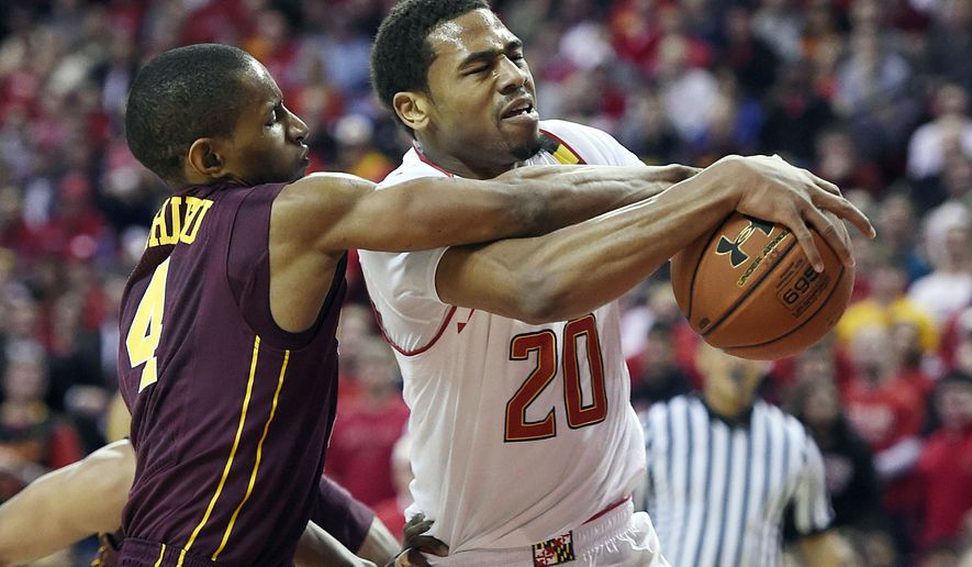 Maryland guard Richaud Pack, right, drives to the basket as  Minnesota guard Deandre Mathieu defends during the first half of  an NCAA college basketball game, Saturday, Jan. 3, 2015, in College Park, Md. (AP Photo/Gail Burton)