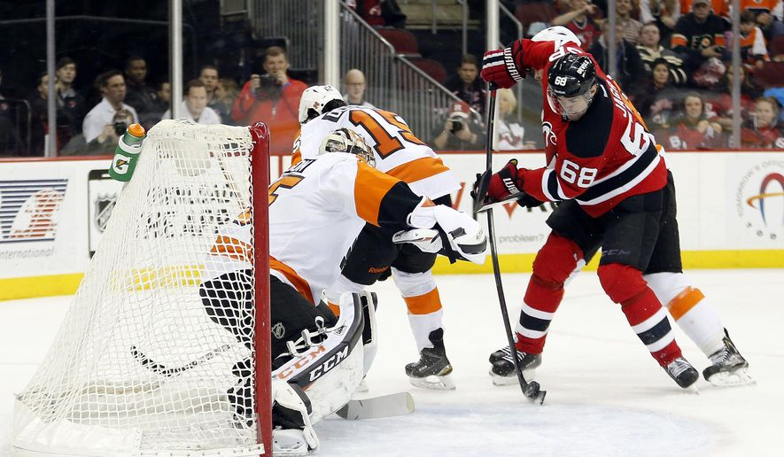 New Jersey Devils right wing Jaromir Jagr (68), of the Czech Republic, scores a goal against Philadelphia Flyers goalie Steve Mason, left, during the second period of an NHL hockey game, Saturday, Jan. 3, 2015, in Newark, N.J. (AP Photo/Julio Cortez)