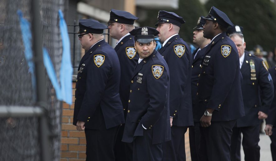 New York Police Department officers arrive for the wake of Officer Wenjian Liu, outside Aievoli Funeral Home, Saturday, Jan. 3, 2015, in the Brooklyn borough of New York. Liu and his partner, Officer Rafael Ramos, were killed Dec. 20, as they sat in their patrol car on a Brooklyn street. The shooter, Ismaaiyl Brinsley, later killed himself. (AP Photo/John Minchillo)