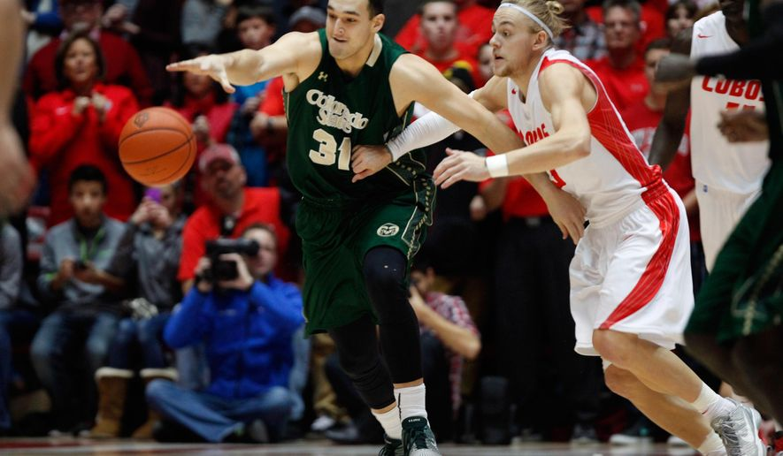 New Mexico's Hugh Greenwood, right, and Colorado State's J.J. Avila chase a loose ball in the first half of an NCAA college basketball game Saturday, Jan. 3, 2015, in Albuquerque, N.M. (AP Photo/Eric Draper)