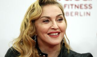 "FILE- In this Thursday, Oct. 17, 2013 file photo, U.S. pop star Madonna smiles during her visit at the ""Hard Candy Fitness"" center in Berlin. Madonna is defending herself against criticism after she posted Instagram photos of Martin Luther King Jr. and Nelson Mandela that were altered to look like her own image on her new album. (AP Photo/Michael Sohn, File)"