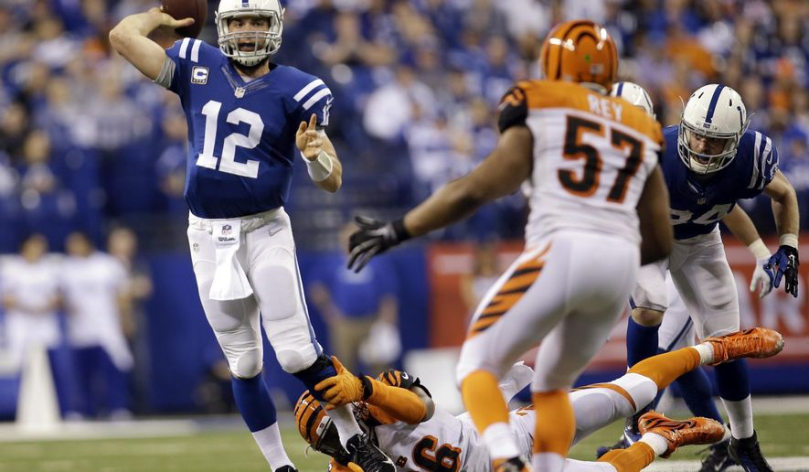 Indianapolis Colts quarterback Andrew Luck (12) throws a 36-yard touchdown pass as he is tackled by Cincinnati Bengals' Carlos Dunlap (96) during the second half of an NFL wildcard playoff football game Sunday, Jan. 4, 2015, in Indianapolis. (AP Photo/AJ Mast)