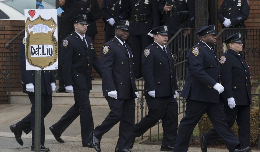 Officers of the 85th Precinct arrive at the wake of New York Police Department officer Wenjian Liu at the Aievoli Funeral Home, Saturday, Jan. 3, 2015, in the Brooklyn borough of New York. Liu and his partner, officer Rafael Ramos, were killed Dec. 20 as they sat in their patrol car on a Brooklyn street. The shooter, Ismaaiyl Brinsley, later killed himself. (AP Photo/John Minchillo)