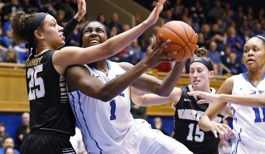 Duke's Elizabeth Williams (1) goes to the basket against Wake Forest's Dearica Hamby (25) as Duke's Azura Stevens, right, and Wake Forest's Millesa Calicott (15) during the second half of an NCAA college basketball game, Sunday, Jan. 4, 2015 in Durham, N.C. (AP Photo/Ellen Ozier)