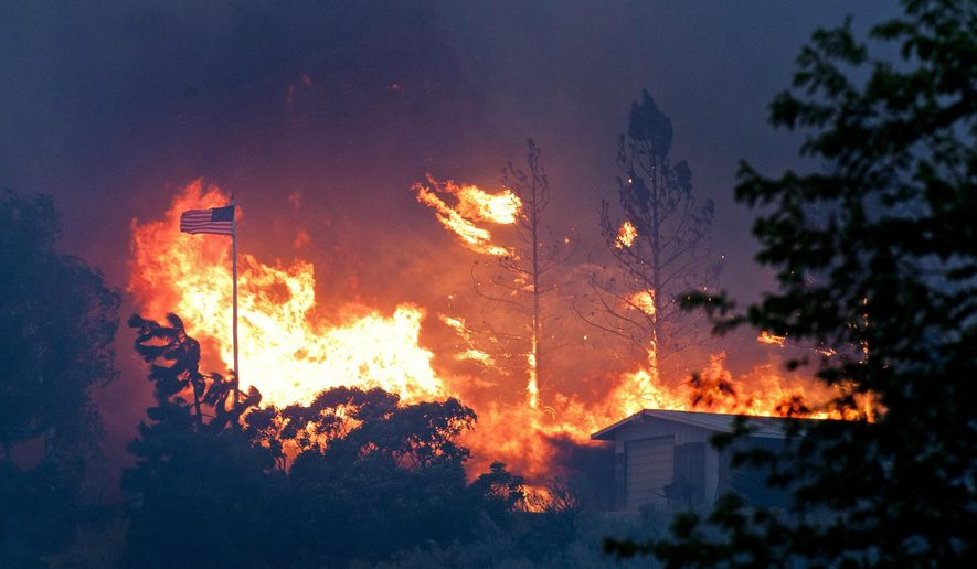 in this July 18, 2014, file photo, an American flag waves in the breeze as a wildfire approaches through trees in Malott, Wash. (AP Photo/The Spokesman-Review, Tyler Tjomsland, File)
