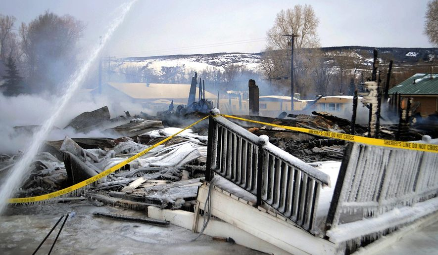 Snow coats the ruins of the historic Royal Hotel, a more than 100-year-old building that still was serving as a residence, hotel and social bar in Yampa, Colo., Sunday, Jan. 4, 2015, after it was destroyed by a fire that began late Saturday. No injuries were reported. According to Steamboat Today two cars parked outside the hotel were destroyed and the adjacent U.S. Post Office and church suffered broken windows and water damage. (AP Photo/Steamboat Pilot & Today, Ben Ingersoll)