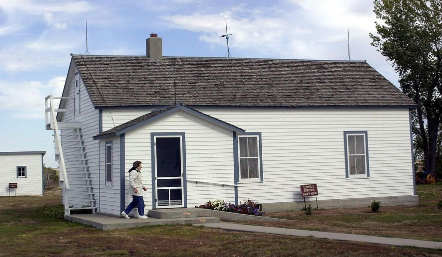 FILE - In this Oct. 10, 2002, file photo Edna Schwab walks toward the front door of the Lawrence Welk farm house in Strasburg, N.D., where Welk taught himself to play accordion. The Legislature earlier this year included $100,000 in the Historical Society budget to buy the property, but lawmakers stipulated that repairs must be made before the purchase. But slipping oil prices may temper the pork party when the Legislature begins its new session Tuesday, Jan. 6, 2015.  (AP Photo/Will Kincaid, File)