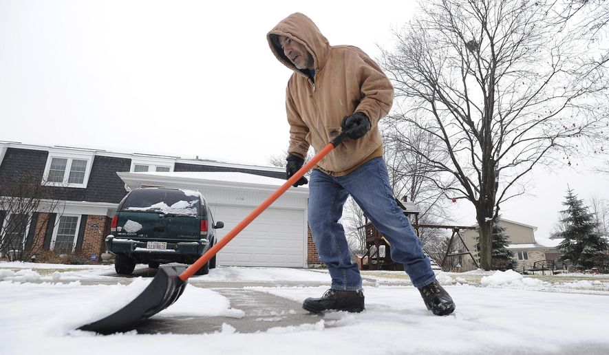 Sal Evola of Arlington Heights dons his winter coat and snow shovel and pushes the wet rainy mess away from his driveway and sidewalks around his house as winter decided to show up after all on Saturday, Jan. 3, 2015. (AP Photo/Daily Herald, Mark Welsh) MANDATORY CREDIT, MAGS OUT, TV OUT