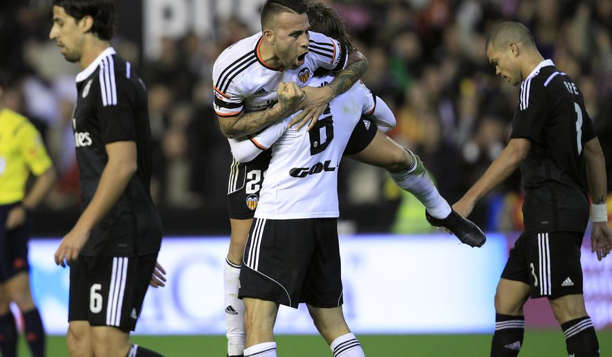 Valencia's Nicolas Otamendi, from Argentina, top center, celebrates his victory at the end a Spanish La Liga soccer match against Real Madrid at the Mestalla stadium in Valencia, Spain, on Sunday, Jan. 4, 2015. Valencia won the match 2-1. (AP Photo/Alberto Saiz) is greeted by teammates