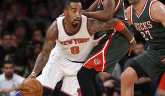 New York Knicks guard J.R. Smith (8) drives around Milwaukee Bucks forward Khris Middleton (22) as Bucks center Zaza Pachulia (27) looks on in the first half of an NBA basketball game at Madison Square Garden in New York, Sunday, Jan. 4, 2015. (AP Photo/Kathy Willens)