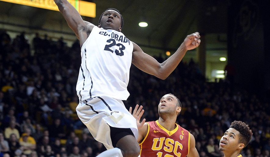 Jaron Hopkins, of Colorado, scores past  Julian Jacobs, of Southern California, during the first half of an NCAA college basketball game, Sunday, Jan. 4, 2015 game in Boulder, Colo. (AP Photo/Daily Camera, Cliff Grassmick)
