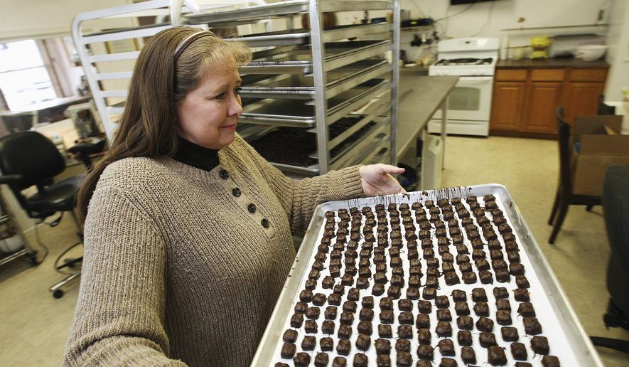 In this Dec. 11, 2014 photo, Amy Wertheim repositions a tray of chocolates while working at R.G.W. Candy Company near Atlanta, Ill. Amy is the daughter of owner Tom Wertheim. (AP Photo/Herald & Review, Jim Bowling)
