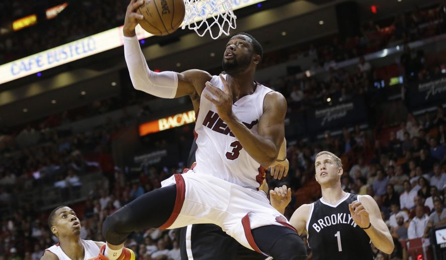Miami Heat guard Dwyane Wade (3) shoots in front of Brooklyn Nets center Mason Plumlee (1) during the first half of an NBA basketball game, Sunday, Jan. 4, 2015, in Miami. (AP Photo/Lynne Sladky)