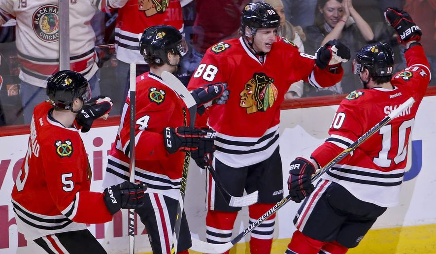 Chicago Blackhawks right wing Patrick Kane (88) celebrates with teammates a goal against the Dallas Stars during the second period of an NHL hockey game in Chicago, Sunday, Jan. 4, 2015. (AP Photo/Kamil Krzaczynski)