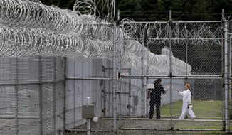 A correctional officer directs an offender through a gate at the Washington Corrections Center For Women in Gig Harbor, Wash., on Oct. 17, 2014. (Associated Press) **FILE**