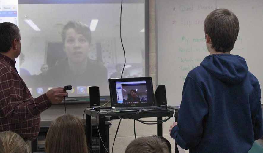 In this Nov. 26, 2014 photo, Elgin Scherff, an eighth-grade student at Ss Peter and Paul Catholic School in Waterloo, Ill., speaks during a videoconference with a student from Norway. It was part an international studies class taught by Bill Theobald, a retired Waterloo School District teacher who stepped back into the classroom this year to educate the students on different countries, cultures and communities. (AP Photo/Belleville News-Democrat, Derik Holtmann)
